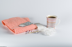 Blanket, medicine, tissues, and a mug of tea or coffee