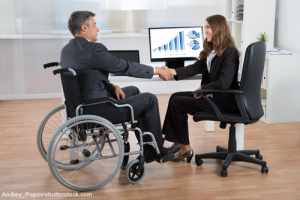 Man in wheelchair shaking hands with woman sitting in front of computer