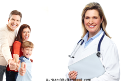 Woman doctor standing next to a family of three giving a thumbs up